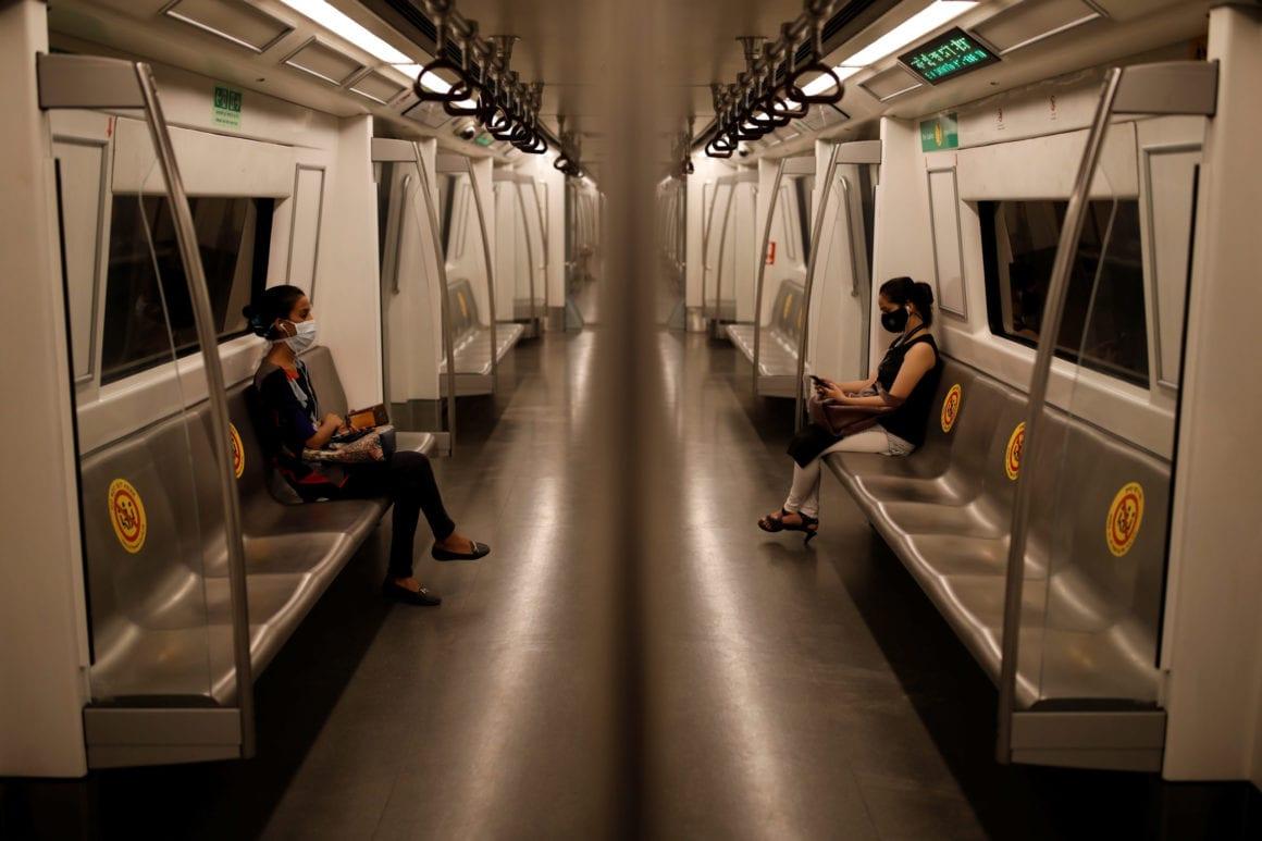 Passengers wearing face masks travel on a Delhi metro train