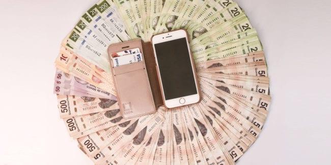 A smartphone over some Mexican pesos