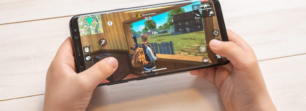 A kid playing Free Fire on a cell phone